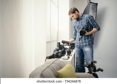 Photographer in his studio, he is holding a digital camera and choosing the right lens for his photo shoot