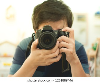 Photographer holding camera in both hand ready to shoot.  Artist look through camera lens focus on shooting. Photograph image.
