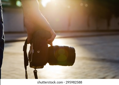 photographer holding a camera in the city with night-lighting