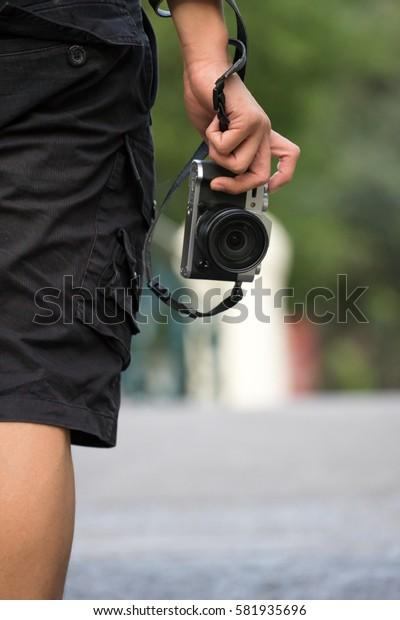 photographer holding camera, close-up. Back view, Soft focus