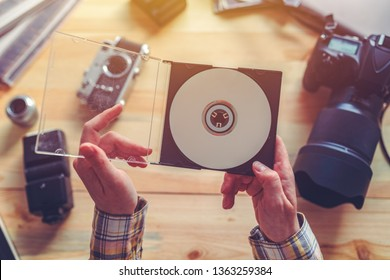 Photographer holding dvd disc with archived photos in photography studio