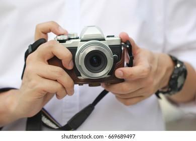 Photographer holding mirrorless camera