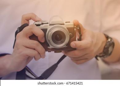 Photographer holding mirrorless camera, vintage style