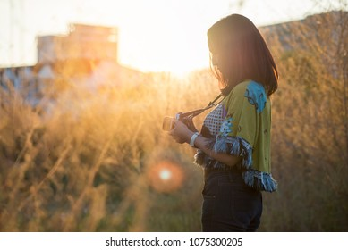 Photographer holding mirrorless camera and woman take photo.People side view,Asian traveler female sightseeing with old camera against sunset background.Travel and Photographer concept.