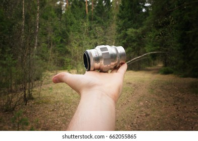 Photographer holds a lens in his hand in a forest, lifestyle