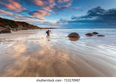 Photographer kneeling with camera on tripod. Moeraki Boulders beach at sunrise, South Island, New Zealand