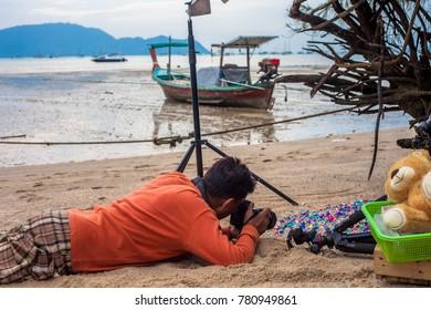 A photographer lay down on the beach to shoot a photo on the beach