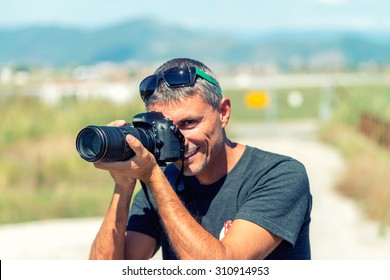Photographer with long zoom lens outdoor.