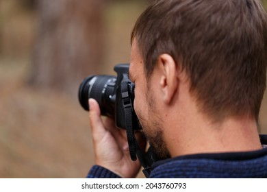 The photographer looking through the viewfinder of a digital camera. The concept of the photography process. Selective soft focus. The photographer takes pictures of nature, landscapes
