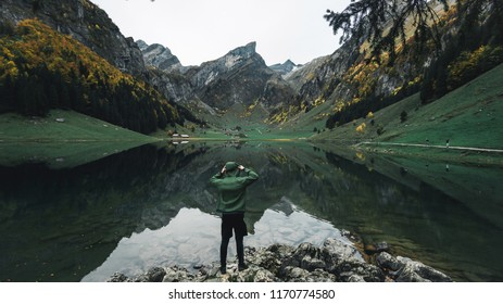Photographer looks into the landscape and listen the silence. Man prepare camera to takes impressive photos of panorama of the mountains lake with it`s reflection, Seealpsee, Switzerland