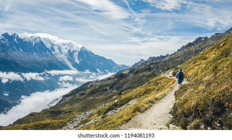 Photographer looks into the landscape and listen the silence. Man prepare camera to take impressive photos of misty fall mountains. Giant mountains in France, Chamonix Mont-Blanc