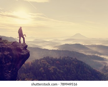 Photographer looks into the landscape and listen the silence. Man prepare camera to takes impressive photos of  misty fall mountains.