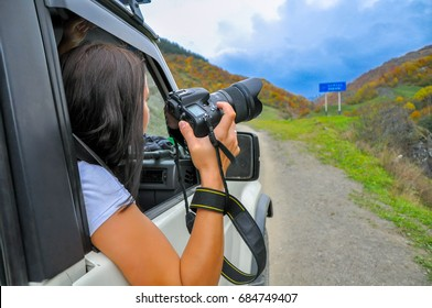 photographer looks out with the camera of the moving car, in search of a good shot