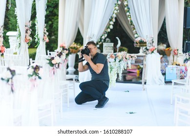 photographer making photos of wedding decoration at white arbor
