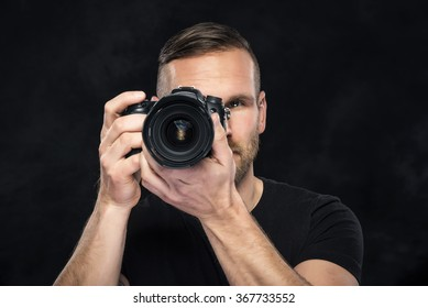 Photographer man with camera on darck background. Focus on model.