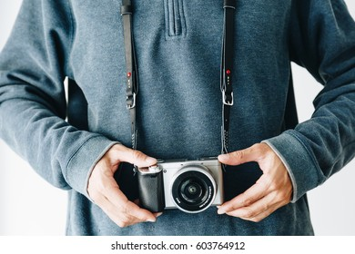 Photographer man with leather camera strap and mirrorless camera on white background