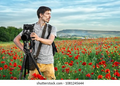 Photographer man on the field of red poppies