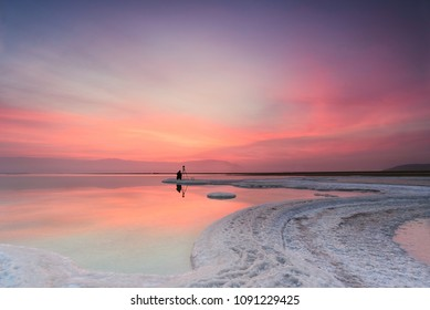 A photographer man shooting the landscape on the edge of the salt shore in the Dead Sea at sunrise with beatiful colors