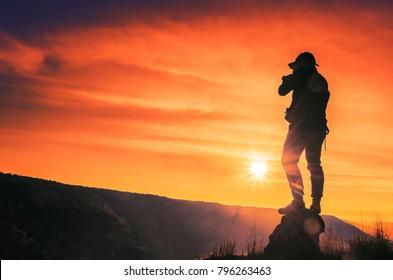 photographer man shooting mountain orange light at sunset.
