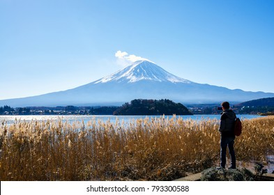 Photographer man standing outdoor photography by mobile amidst the beautiful nature of Mt. Fuji at Yamanashi in Japan with lake kawaguchiko. Travel and Attractions Concept.