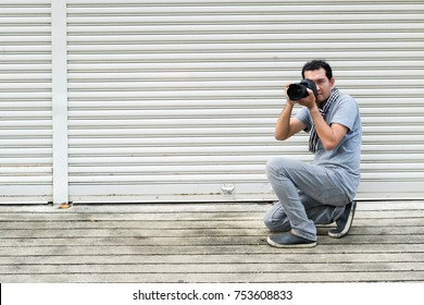 Photographer  man young shooting have fun on steel sheets background.