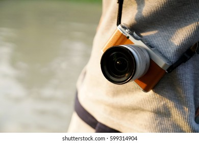 Photographer with mirrorless camera. Standing outdoors with the camera hanging on the shoulder