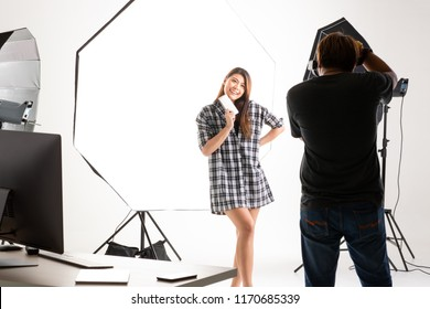 Photographer and model working in modern lighting studio with many kinds of flash and accessories.