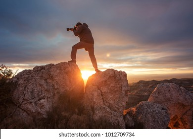 photographer in mountain at sunset