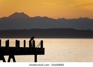 A photographer and the Olympic Mountains. Photographing a dramatic sunset over the Olympic Mountains from Alki beach in Seattle, Washington.