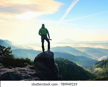 Photographer  on cliff. Nature photographer takes photos with mirror camera on peak of rock. Dreamy fogy landscape, spring orange pink misty sunrise in a beautiful valley below.