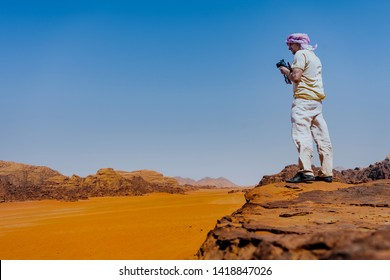 Photographer on cliff and thinking. Dreamy foggy landscape orange misty sunrise in a beautiful valley below on desert. Taken on top Wadi Rum desert in Jordan