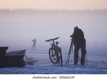 Photographer on a foggy day with a bicycle and winter equipment photographing a skier in winter.