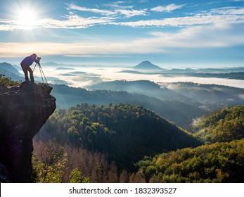 Fotograf auf Berghexe durch Sucher. Naturfotograf, der von der Bergspitze aus die schöne Morgenlandschaft fotografiert