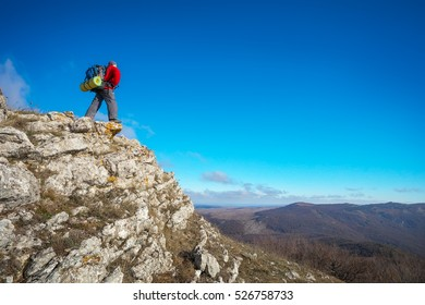 Photographer on top of the mountain in autumn. Traveler with backpack enjoying a view from the mountain top