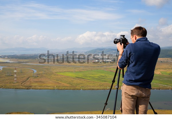 Photographer on top of the mountain to shoot panoramas of the Gulf Nakhodka (old name of the Gulf of America) and the city of Nakhodka. Far East, Primorsky Krai, Russia.