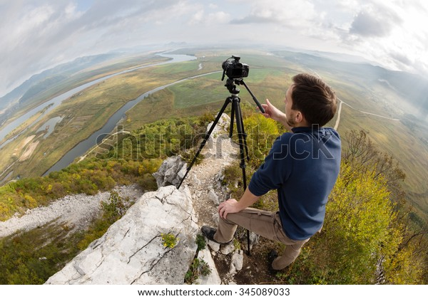 Photographer on top of the mountain takes a neighborhood on the camera. Taken with a fisheye lens.