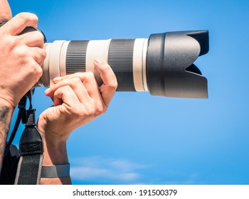 Photographer outdoors with big zoom digital lens as professional equipment getting ready to shoot a photo