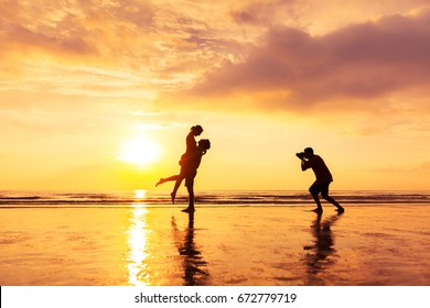 Photographer photographing a loving couple on the beach in summer