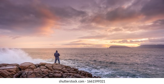 Photographer photographing waves crashing on rocks with amazing sunrise in background. Fanad Head peninsula at Wild Atlantic Way, Donegal, Ireland