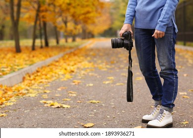 Photographer with professional camera outdoors on autumn day, closeup. Space for text