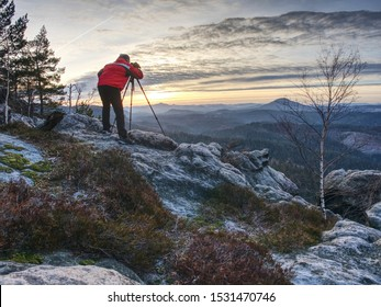 Photographer in red jacket and knitted cap stay with camera on tripod on cliff and thinking. Dreamy misty landscape, misty sunrise