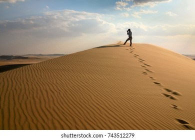 Photographer in sand dunes of Grand Sand Sea during desert safari in Egypt close to oasis Wahat Siwa