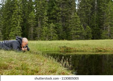 Photographer shooting a macro scene by a lake