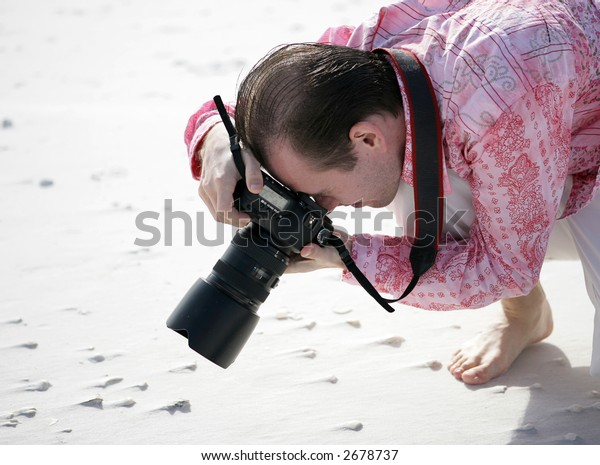 A photographer shooting a macro of shells on the beach.