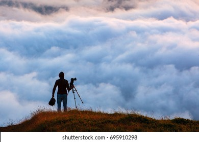Photographer shooting natural phenomenon - the clouds that roam the mountains. Concept theme: nature, weather, tourism, extreme, healthy lifestyle, adventures. Unrecognizable persones.