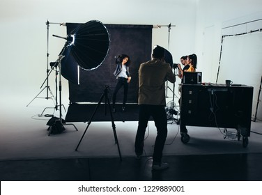 Photographer shooting photos of a female model with studio flash lights on. Photographer with his team during a photo shoot.
