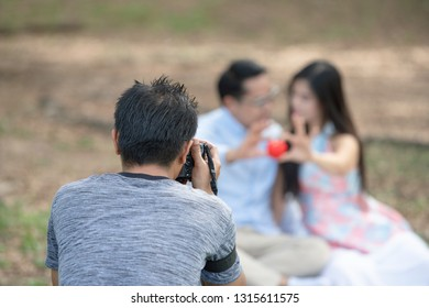 photographer is shooting a pre-wedding album for a married couple. Behind the scenes of camera shooting or video production and film crew team with camera equipment on location.