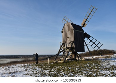 Photographer shoots a winter view by an old windmill in a wintry landscape at the swedish island Oland
