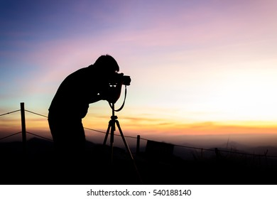 Photographer silhouette above a clouds sea, misty mountains in twilight time