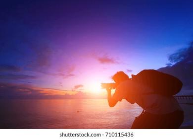 Photographer silhouette at beautiful sunrise.